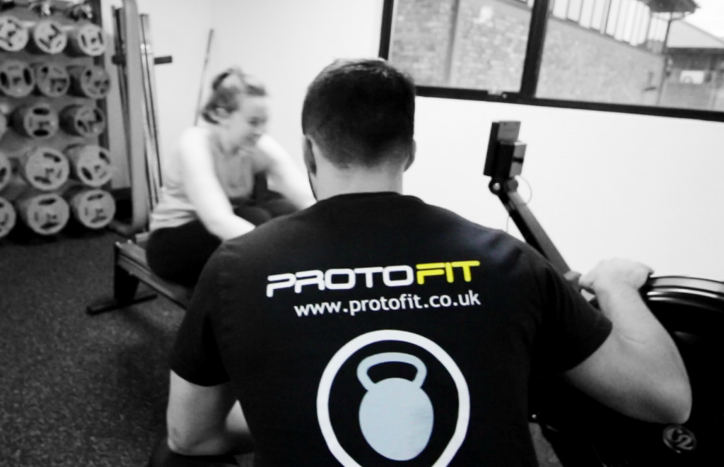 Head Coach Rob coaching a client on the Rower.